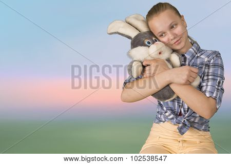 Teen girl embracing the plush toy on blurry background
