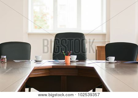 Colored Pencils And Three Cups Of Coffee On The Background Of The Three Chairs In An Office Conferen