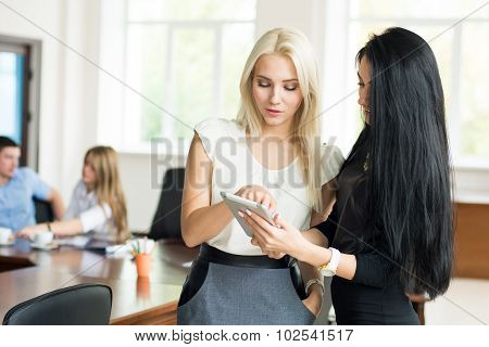 Two Young Business Woman With Tablet Computer In The Office To Discuss The Problem At A Business Mee