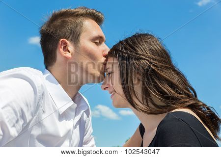 Young Attractive Caucasian Couple Man Kisses Woman On Forehead
