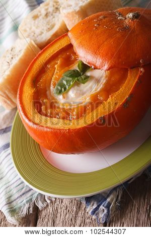 Delicious Soup In A Pumpkin Close-up On The Table. Vertical