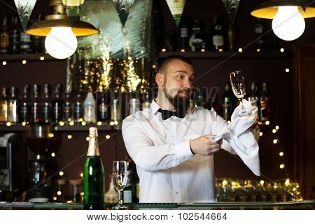 Bartender wipes glasses at work