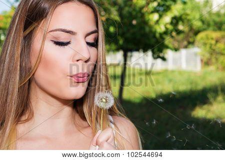 Beautiful brunette blowing dandelion