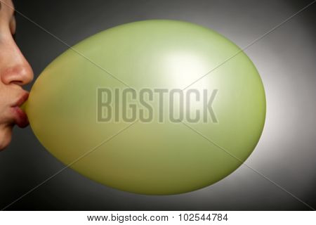 Young woman inflating balloon on gray background