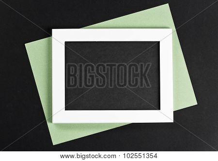 Horizontal White Photo Frame With Black Field And Green Paper Under Angle On Black Background Isolat