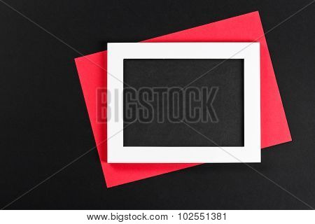 Horizontal White Photo Frame With Black Field And Red Paper Under Angle On Black Background Isolated