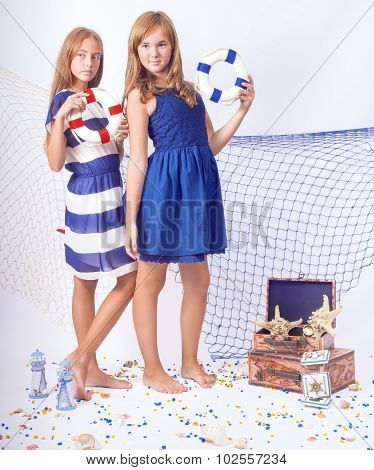 Two beautiful teen girls standing with lifebuoys