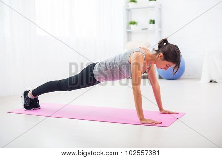 fit woman doing push-ups on the floor in her living room an exercise mat at home