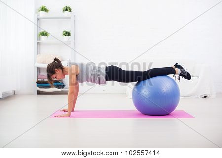 Woman doing push-ups on the floor with fit ball in her living room an exercise mat at home