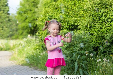 Little Girl With Pigtails Blows Soap Bubbles