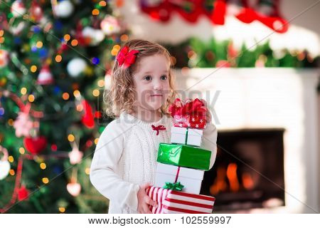 Little Girl Opening Christmas Presents At Fire Place