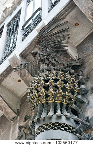 BARCELONA, SPAIN - MAY 02: Ornate Phoenix sculpture, Palau Guell, Barcelon , Spain mounted on the exterior front facade between arched doors allowing entry of horse drawn carriages, May 02, 2015