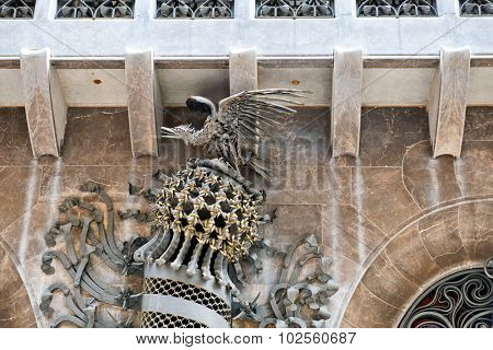 BARCELONA, SPAIN - MAY 02: Phoenix sculpture between the arches allowing horse drawn carriages to enter the building on Palau Guell, Barcelona , Spain designed by Antoni Gaudi, May 02, 2015