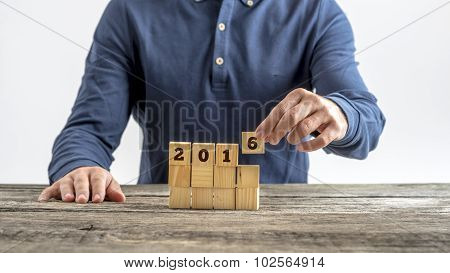 Front View Of A Man Assembling A 2016 Sign With Wooden Cubes