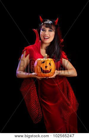 Woman In Halloween Costumes Of Devils Holding A Pumpkin At The Black Background.