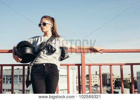 Young Female Biker Holding Motorcycle Helmet