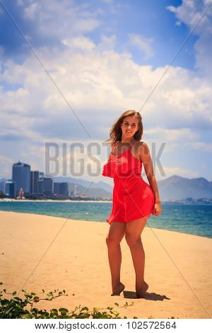 Blond Girl In Red Stands Barefoot On Sand Touches Hip Under Wind