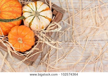 Overhead view of a wooden crate with different decorative pumpkins on a rustic wood table with straw. Horizontal format with copy space.