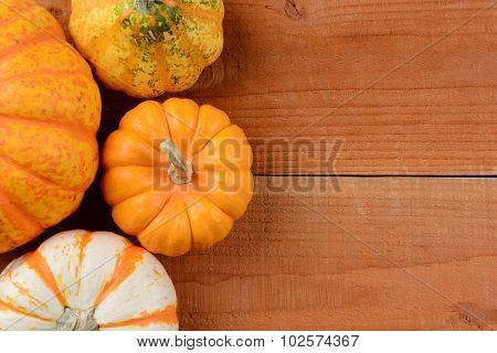 high angle view of a group of ornamental gourds on rustic wood planks. Pumpkins and gourds for Thanksgiving decorations with copy space.