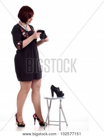 Brunette Girl In Black Dress Examines Black Shoes