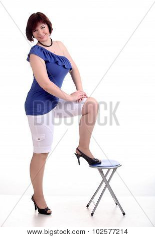 Brunette Girl In Blue Blouse And White Shorts Puts One Foot On Low Chair