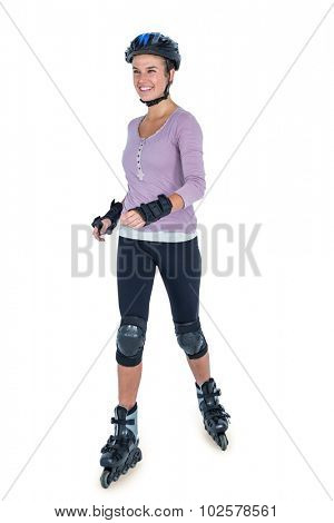 Young woman inline skating over white background