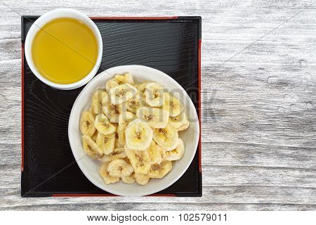 Set of Crunchy banana chips and hot tea on wood table background