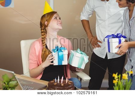 Smiling businesswoman receiving birthday gifts from colleagues in office