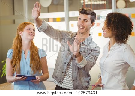 Smiling businessman gesturing while female colleagues looking at him in office