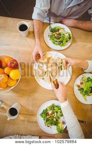Cropped image of business people having brunch in canteen at creative office