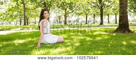 Panoramic view of park while young woman sitting on grassland