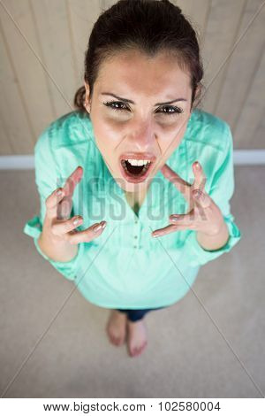 High angle portrait of screaming woman gesturing while standing by wall at home