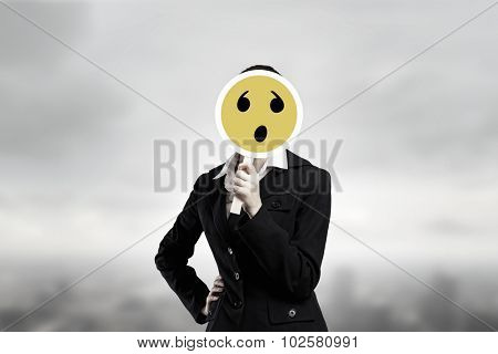 Unrecognizable businesswoman hiding her face behind sad mask