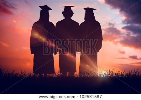 Three students in graduate robe holding a diploma against orange and blue sky with clouds