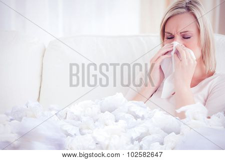 Woman blowing her nose against used tissues