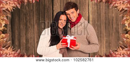 Young couple holding a gift against close-up of wooden plank