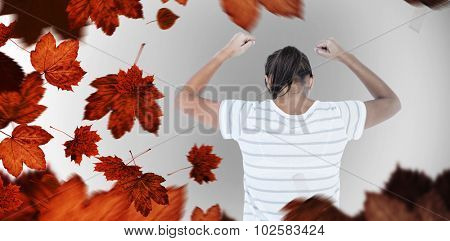Depressed woman with hands raised against autumn leaves