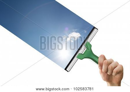 Hand using wiper against blue sky with clouds