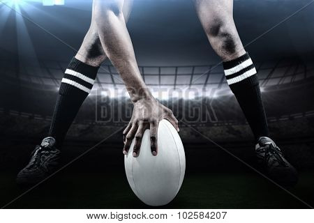 Low section of sportsman playing rugby against rugby stadium