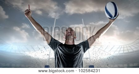 Successful rugby player holding ball with arms raised against rugby stadium