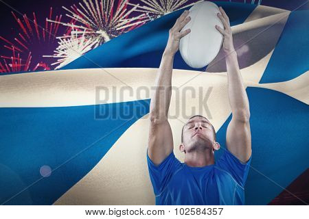 Rugby player holding ball with eyes closed against fireworks exploding over football stadium