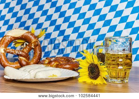 Glass Full Of Beer With Prezels And Traditional Bavarian Sausage In Front Of Bavarian Flag