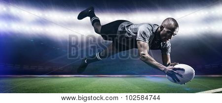 Sportsman jumping for catching rugby ball against rugby stadium
