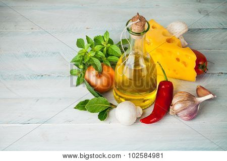 Olive oil with spices and vegetables on wooden board