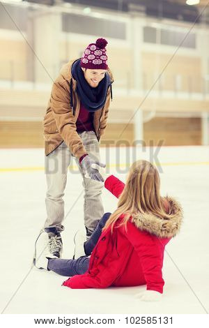 people, friendship, sport and leisure concept - smiling man helping women to rise up on skating rink