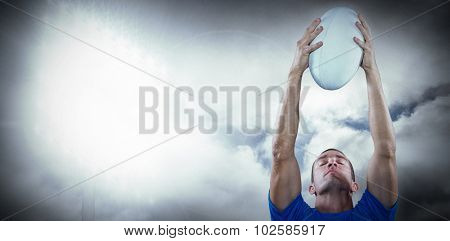 Rugby player holding ball with eyes closed against spotlight in sky