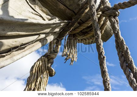Old ragged sailing rigging an ancient sailing vessel against cloudy sky