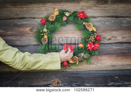 Girl arm holding red bow and decorating rustic log cabin wall with X-mas wreath