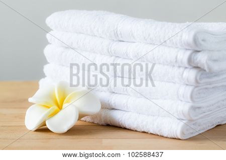 Plumeria flower with stack of white towel