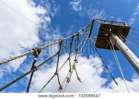 Old rope ladder and mast against cloudy sky